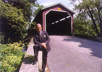 John Pyfer standing in front of a covered bridge