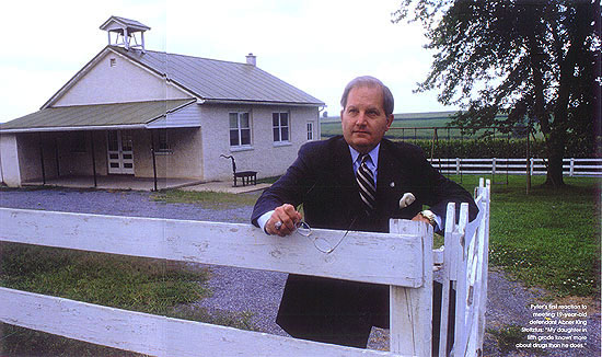 John Pyfer standing behind a fence