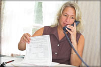 woman talking on phone and reviewing documents