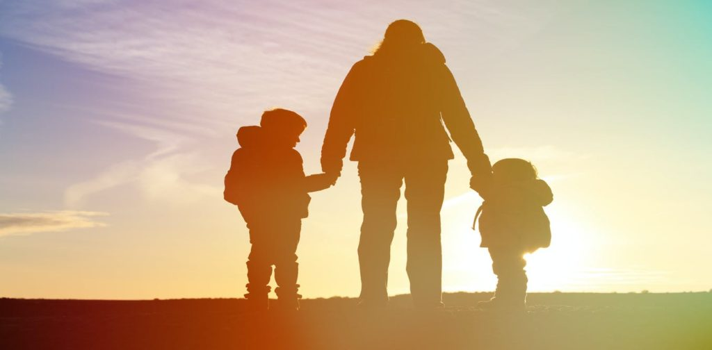 a silhouette of a parent with two small children