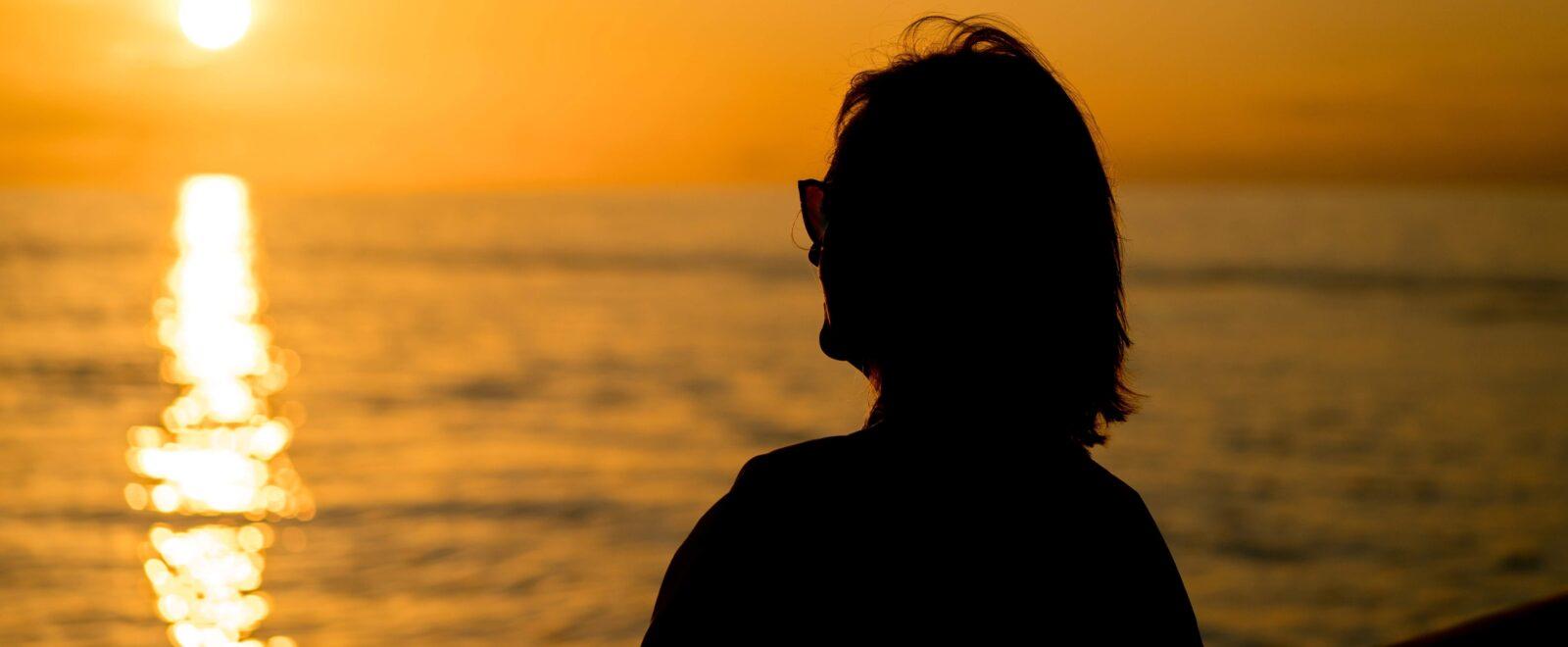 retired woman sitting on beach
